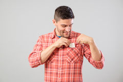 Man takes out blank business card from the pocket. Young man takes out blank business card from the pocket of his shirt isolated on gray background Stock Images