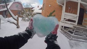 A man takes out a blue icy heart from a snowdrift. It clears the ice of snow. First-person view.
