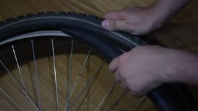 A man takes out a camera from a bicycle wheel. A man takes out a camera from a bicycle wheel stock footage