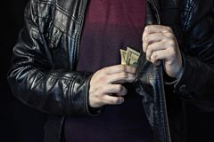 A man takes out money from a breast pocket, a black background, a black jacket stock photography
