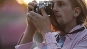 Man Takes Photo. Attractive young man with fair dreadlocks taking photo, having amateur shoot after tiring working day, outdoor in urban area stock video