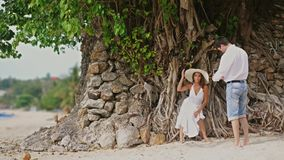 Man takes photo of beautiful woman in hat and white dress on a camera Outdoors Under the Tree with roots. Happy smiling. Man Taking photo of beautiful woman in stock video