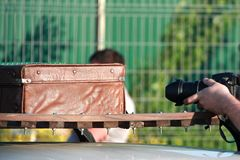 Man takes a photo of brown vintage leather suitcase.  stock images