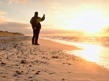 Man takes photo of  evening sea. Hiker with backpack with phone in hand along beach. Stock Photos