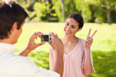 Man takes a photo of his friend giving the peace sign Stock Photo