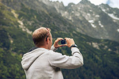 Man takes a photo of mountain landscape Royalty Free Stock Image