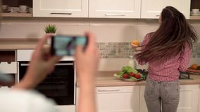 Man Takes Photo of Woman. Good-looking man taking photo of joyful woman with oranges, young beautiful woman wearing checked red shirt and casual jeans, indoor stock footage