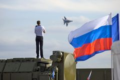 A man takes photos of airplane. Russian state flag tricolor. ZHUKOVSKY, MOSCOW REGION, RUSSIA - AUGUST 28, 2015: A man takes photos of airplane. Russian state stock photo