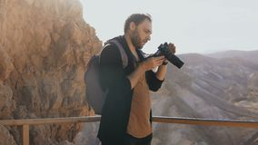 Man takes photos of massive mountain scenery. Caucasian male with camera photographs and looks at his camera. Israel 4K. Man takes photos of massive mountain stock video footage