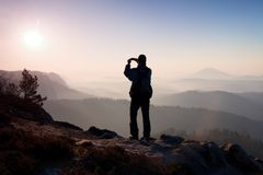 Man takes photos with smart phone on peak of rock empire. Dreamy fogy landscape, spring orange pink misty daybreak Royalty Free Stock Photography