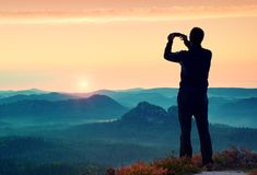 Man takes photos with smart phone on peak of rock empire. Dreamy fogy landscape, spring orange pink misty sunrise above beautiful Royalty Free Stock Photos