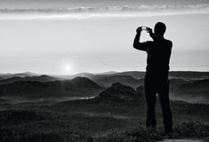 Man takes photos with smart phone on peak of rock empire. Dreamy fogy landscape, spring orange pink misty sunrise above beautiful Royalty Free Stock Images