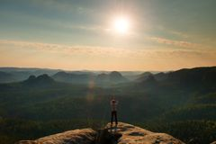 Man takes photos with smart phone on peak of rock empire. Dreamy fogy landscape, spring orange pink misty sunrise in a beautiful v Royalty Free Stock Photos
