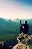 Man takes photos with smart phone on peak of rock empire. Dreamy fogy landscape, spring orange pink misty sunrise in a beautiful v Royalty Free Stock Photography