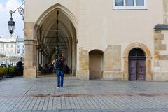 A man takes a picture of arcades in Krakow. Krakow, Poland - May 25, 2017: A man takes a picture of arcades. Arcades of the Cloth Hall are one of the variety of Stock Photography