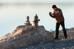 Man takes picture of balancing rocks. On a lake shore stock photography