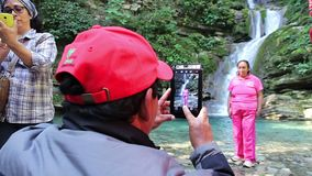 A man takes a picture of his friend, in the background a waterfall. SAN LUIS POTOSI, MEX 2016 (ILLUSTRATIVE IMAGE). A man takes a picture of his friend, in the stock video