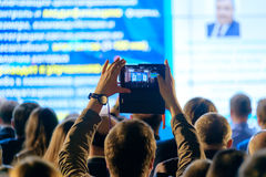 Man takes a picture of the presentation at the conference hall Royalty Free Stock Photos