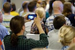 Audience listens to the lecturer. Man takes a picture of the presentation at the conference hall using smartphone Royalty Free Stock Photography