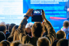 Man takes a picture of the presentation at the conference hall Stock Photos