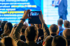 Man takes a picture of the presentation at the conference hall Stock Photo