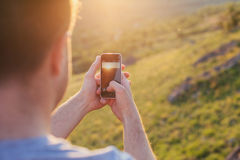 Man takes a picture of sunset Royalty Free Stock Photos