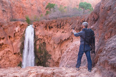 Man takes picture of waterfall with his mobile phone Royalty Free Stock Photos