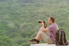 Man takes pictures from a hill in the background of forest.  Stock Image
