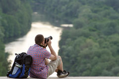 Man takes pictures from a hill in the background of forest and river.  Royalty Free Stock Photography
