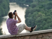 Man takes pictures from a hill in the background of forest and river.  Stock Photos