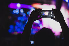 Man takes pictures on his smartphone at concert. Boy makes photo with His smartphone to a concert to share the moment with friends on social networks, image with Stock Image