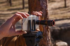 Man takes pictures on the phone with lenses. A man adjusts the smartphone on a tripod with lenses. The photographer travels taking pictures of the landscape Stock Images