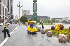 Man takes pictures of a street sweeper and female officer talking at the Tianfu Square. Chengdu, China - September 29, 2017: Man takes pictures of a street stock images