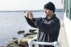 Man takes scenic cell phone photo in Maine harbor Stock Photography