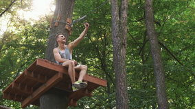 Man takes a selfie on his phone sitting on the tree in a rope park.  stock video footage