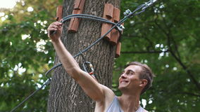 Man takes a selfie on his phone sitting on the tree in a rope park.  stock footage