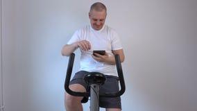Man takes selfies on exercise bike stock video
