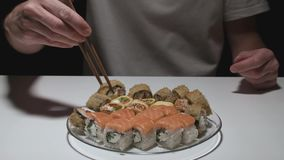 A man takes sushi roll with chopsticks on black background. Cooking stock video