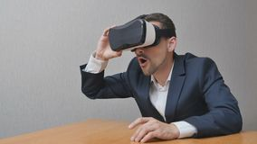 Man takes virtual reality glasses. Admiring man takes virtual reality glasses. Businessman is playing online in 3d. The person uses the technology in work VR 360 Royalty Free Stock Image