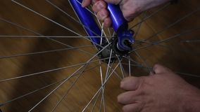 The man takes the wheel off the bicycle. Gets the wheel out of the bicycle fork. The man takes the wheel off the bicycle. Gets the wheel out of the bicycle fork stock video footage