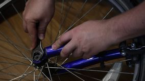 The man takes the wheel off the bicycle. Unscrew the nut with a wrench. The man takes the wheel off the bicycle. Unscrew the nut with a wrench stock video