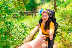 Man takes a woman's hand in a hike Royalty Free Stock Photo