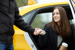 Man takes womans hand to help get out of taxi. Man takes a womans hand to help get out of taxi. Portrait of smiling young business lady Stock Image