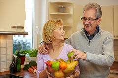 Man taking apple from fruit bowl Royalty Free Stock Images