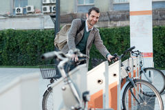 Man taking a bike in a bike sharing. City service Royalty Free Stock Photo