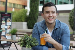 Man taking a break with a cold refreshing orange juice.  Stock Image
