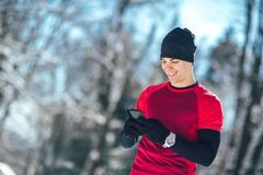 Man Taking Break from Jogging in the Forrest using Smart Phone. Young Man Taking Break from Jogging in the Forrest using Smart Phone Royalty Free Stock Photos