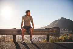 Man taking a break after morning run. Male runner sitting on a guardrail on country road looking away on sunny day. Young man taking a break after morning run Stock Images