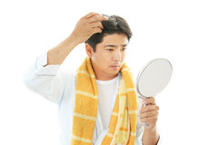 A man taking care of his hair Stock Photos