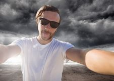 Man taking casual selfie photo in front of dramatic dark cloud landscape Stock Photos